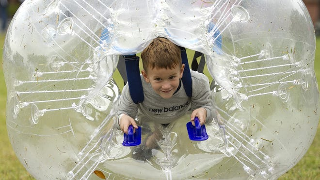 Five-year-old Racin Gerhart rolls around in a plastic bubble during a previous Kids Helping Kids Festival. This year's expanded event takes place Saturday at Alico Family Golf in south Fort Myers.