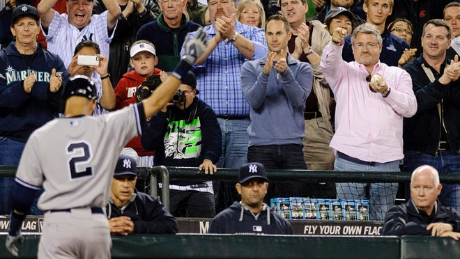 Fans give New York Yankees shortstop Derek Jeter (2) a standing ovation as he walks off the field after being thrown out by the against the Seattle Mariners during the ninth inning at Safeco Field.