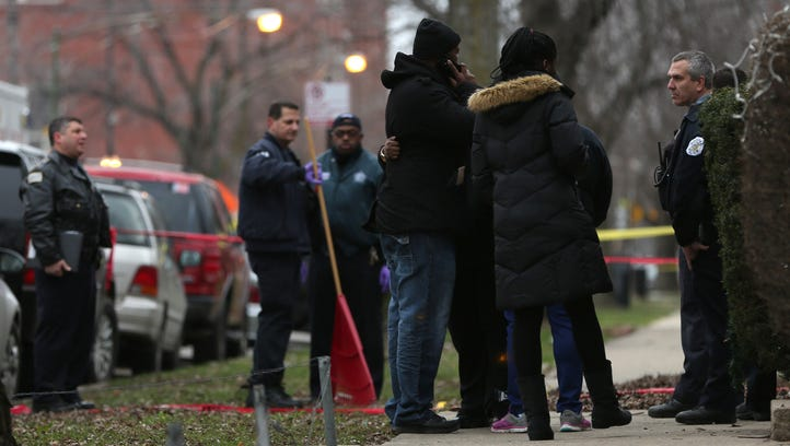 Chicago police officers talk with relatives of one of the two people killed by a police officer, as they investigate a shooting in the entry of their apartment in Chicago Saturday.