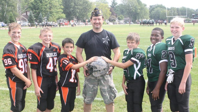 Michigan Military Moms founder Gary Tanner (center) is pictured with (from left) Livonia Orioles junior varsity players Connor Cohan, Conner Bell and Ethan Vanlandingham and Novi Bobcats Cole Shires, Jermeir Reliford and Kyle Dowd.