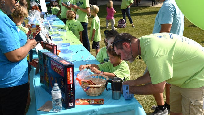 Parents and kids take a look at some of the offerings at the raffle table at the Aug. 26 Back to School Bash at Heritage Park.