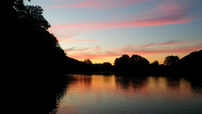 A summer sunset along a river is a great way to end a day of trout fishing.