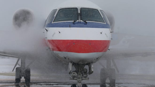 An American Airlines jet is sprayed down in an anti-icing agent prior to takeoff at the Des Moines International Airport on Tuesday, Feb. 4, 2014. (Bryon Houlgrave/The Register)