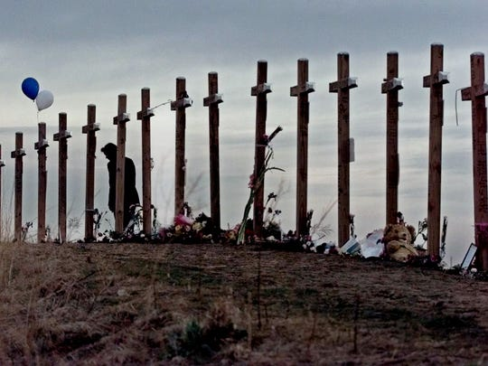 """In this April 28, 1999, file photo, a woman stands among 15 crosses posted on a hill above Columbine High School in Littleton, Colo., in remembrance of the 15 people who died during a school shooting on April 20, 1999. The mother of Columbine High School shooter Dylan Klebold said she didn't know anything was wrong with her son before the 1999 attack, and she prayed for his death when she heard he was involved and that the rampage might still be underway. In an interview that aired on """"20/20"""" late Friday, Feb. 12, 2016, Sue Klebold told ABC News' Diane Sawyer that before the attack she considered herself a parent who would have known something was wrong."""