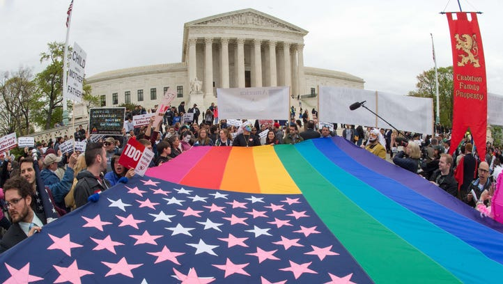 Protesters hold a pro-gay rights flag outside the US