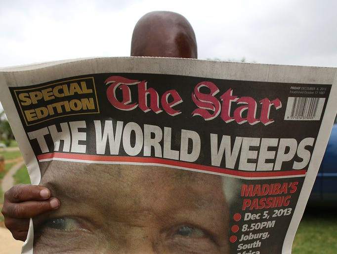 A man reads a local paper on Dec. 6 in Soweto, South Africa. The front page is dedicated to former South African president Nelson Mandela, who died a day earlier in Johannesburg.