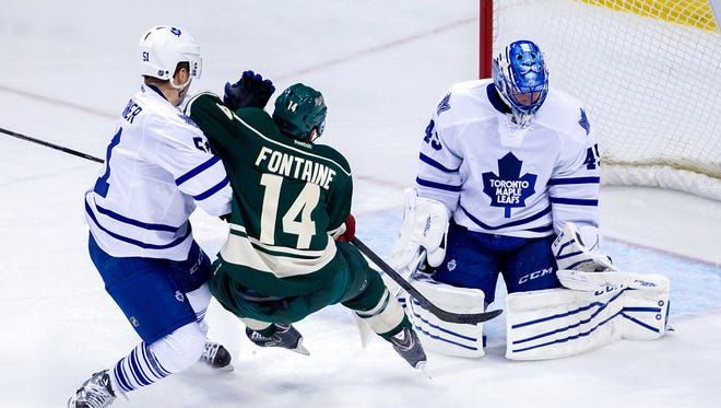 Toronto Maple Leafs goalie Jonathan Bernier (45) makes a save in the third period against the Minnesota Wild right wing Justin Fontaine (14) at Xcel Energy Center.