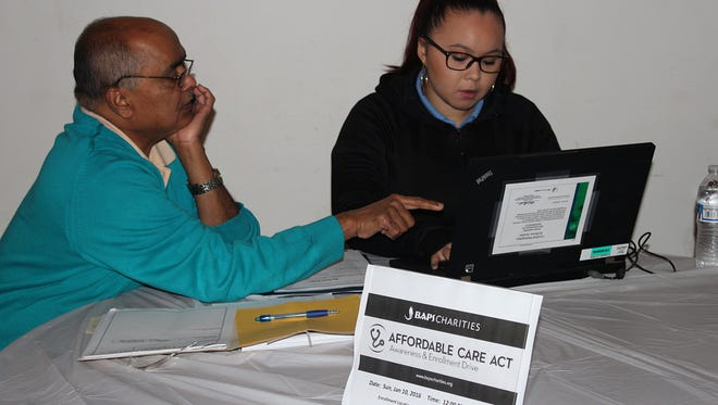 Baps Charities Volunteer Dinesh Patel gets information on health care  plan options.