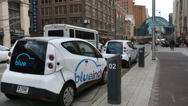 BlueIndy electric cars are parked at the company's charging station on the northeast corner of Meridian and Washington streets, Indianapolis, on Tuesday, Dec. 30, 2014.
