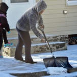 Antonia Hernandez sweeps lingering snow of the sidewalk as her daughter, Daphane, 7, gets ready for school Wednesday, Jan. 13, 2016 in Chambersburg. some residents were still cleaning up from Tuesday evening's snowsquall - the first storm of the season.