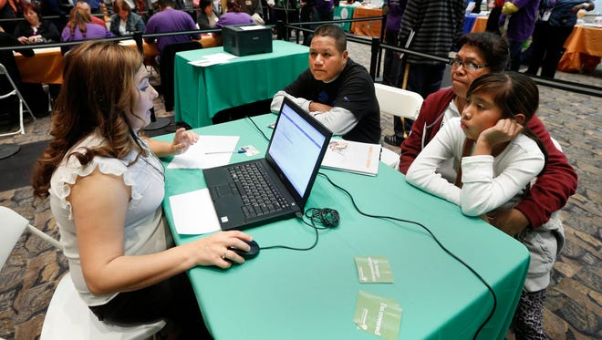 Enrollment counselor  Nancy Gonzalez, left, helps  the Alejo family, Hugo, left, his wife , Emedtiat and daughter Karla, 11, right, sign up for health insurance through the California health insurance exchange  in Sacramento,.