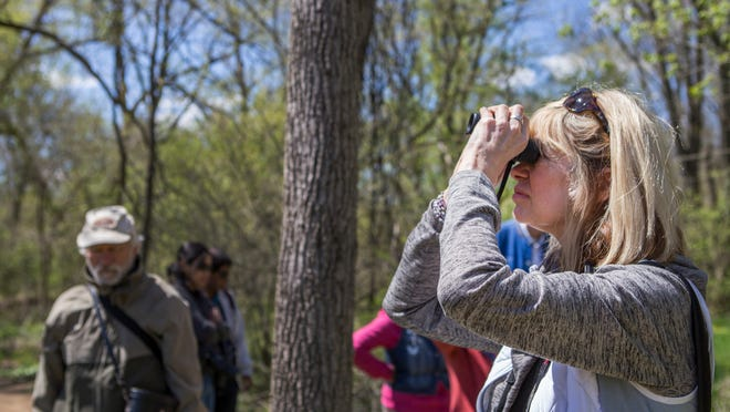 Maggie Favata looks through her binoculars as she joins birdwatchers on a tour of White Clay Creek State Park with The News Journal's environment reporter Molly Murray.