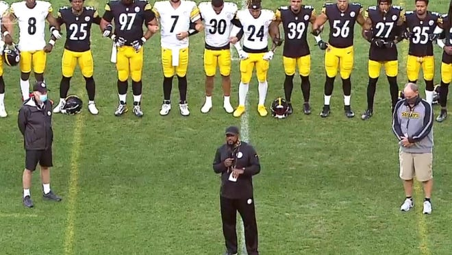 Pittsburgh Steelers coach Mike Tomlin, center foreground, speaks while the players lock arms in unity Friday before evening practice at Heinz Field. Among the players are quarterback Ben Roethlisberger (7) and Erie native James Conner (30). Tomlin spoke about the team's unified stance on issues that are affecting the country. He spoke for about three minutes and the players then gathered in prayer.