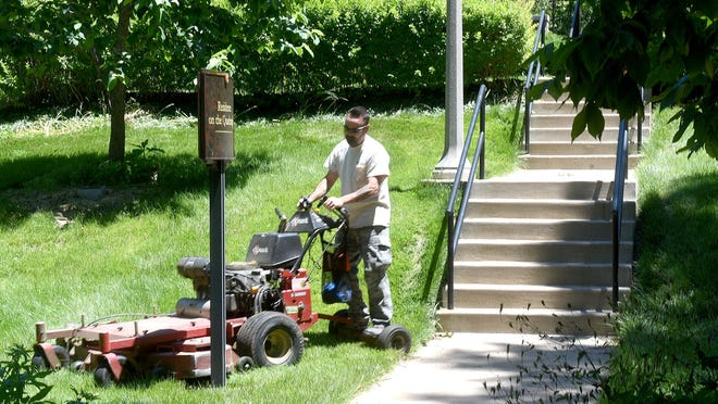 A landscape worker at the University of Missouri mows grass near the chancellor's residence on Wednesday. The university will open bids for private landscaping and custodial services companies to replace MU's landscaping and custodial service to cut costs.