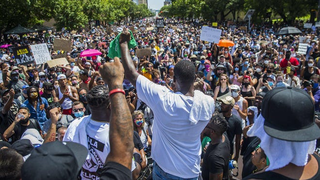 """Thousands of protesters chant, """"Black Lives Matter,"""" while gathered peacefully Sunday on 11th Street in front of the Capitol."""