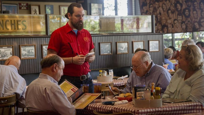 Sam Calliham, left, Anthony Daywood and Vivian Daywood order food from Kile Moore at Threadgill's World Headquarters in 2018. Threadgill's closed permanently in April, weeks after the coronavirus pandemic temporarily shuttered dining rooms.