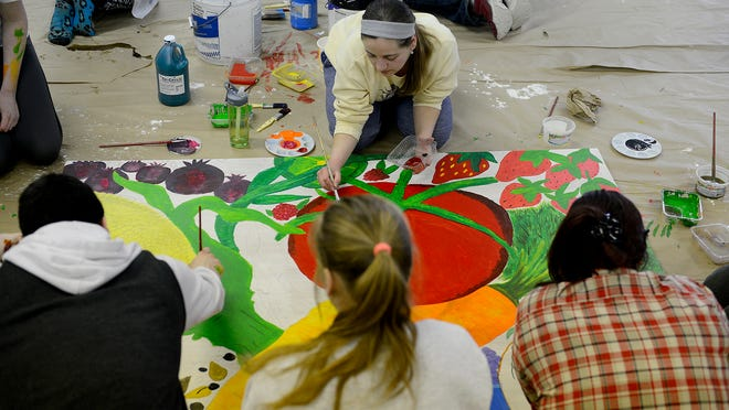 Anne Hooper and other Holt High School seniors paint a mural on Tuesday for the Holt Farmers Market. The murals were designed by students and will be displayed in the market building.