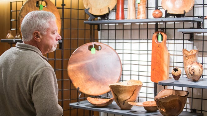 Bill Cushing looks at woodturning works by Philip T. Hauser at the Hagley Craft Fair on Sunday.