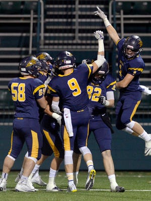 Victor players celebrate their first touchdown during the Section V Class AA final at Rhinos Stadium on Nov. 5, 2016.