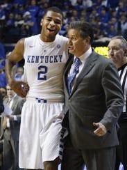 Kentucky's Aaron Harrison (2) is hugged by head coach