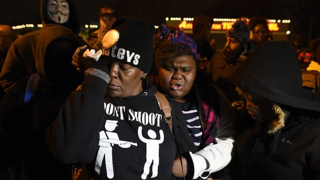 A demonstrator wipes her eyes as she joins other to say a prayer in front of the police station in Ferguson, Missouri, on November 24, 2014.