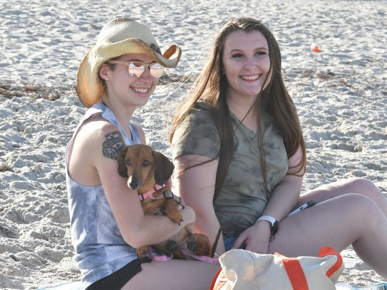 Tabitha Headlee and Alex Smith pose with Poob, a dachshund