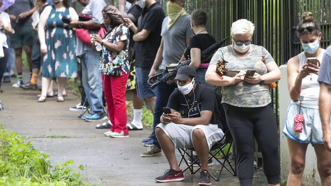 FILE - In this June 9, 2020, file photo, Steven Posey checks his phone as he waits in line to vote at Central Park in Atlanta.
