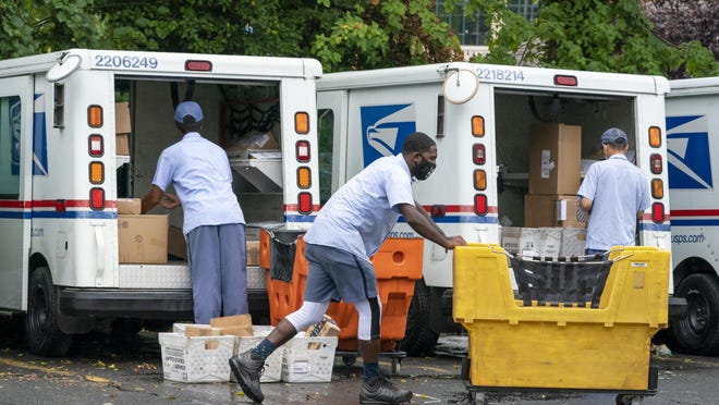 Letter carriers load mail trucks for deliveries at a U.S. Postal Service facility in McLean, Va., Friday, July 31, 2020. President Donal Trump has repeatedly raised unsubstantiated fears of fraud involving mail-in voting, which is expected to be more widely used in the November election out of concern for safety given the COVID-19 pandemic.