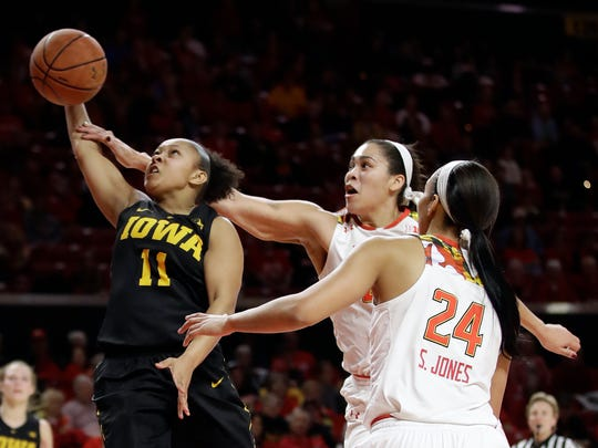 Iowa guard Tania Davis, left, is fouled by Maryland center Brionna Jones, center, as she shoots against Jones and Maryland forward Stephanie Jones (24) in the first half of an NCAA college basketball game, Sunday, Jan. 29, 2017, in College Park, Md.