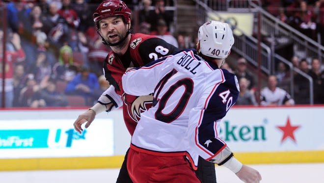 Arizona Coyotes left wing John Scott, left, fights with Columbus Blue Jackets right wing Jared Boll.