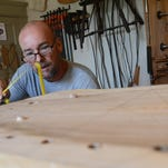John Rowe and instructor Kurt Lewin, center, look over John Thompson as he drills holes in the seat of a Windsor chair at Lewin's workshop inside Windsor House in Capeville, Va. Wednesday, Aug. 19, 2015. Lewin, who has been making Windsor chairs by hand for more than a decade, teaches Windsor chair making classes year round.