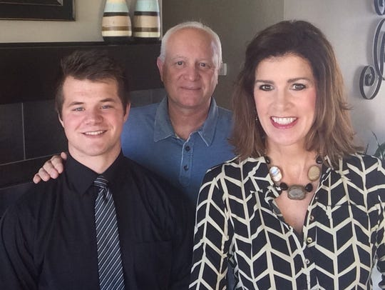 Sergei Neubauer, left, with his parents, Larry Loss