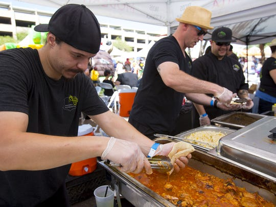 David Gonzales, left, Kyle Mason, and Angel Varges, from Modern Margarita make pork tacos during the sixth annual Rockin' Taco Street Fest at Dr. AJ Chandler Park in Chandler on Sept. 16, 2017.
