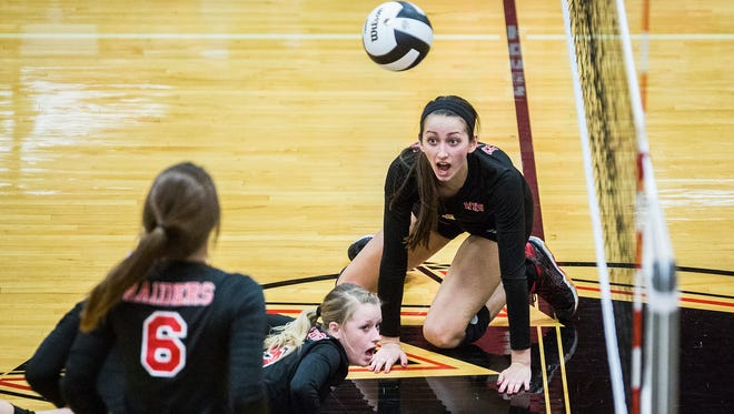 Wapahani's Skyler Van Note, right, and Erin Roach, center, react to saving a point during their regional game at Wapahani High School Tuesday, Oct. 25, 2016. The Raiders defeated Alexandria 3-0.