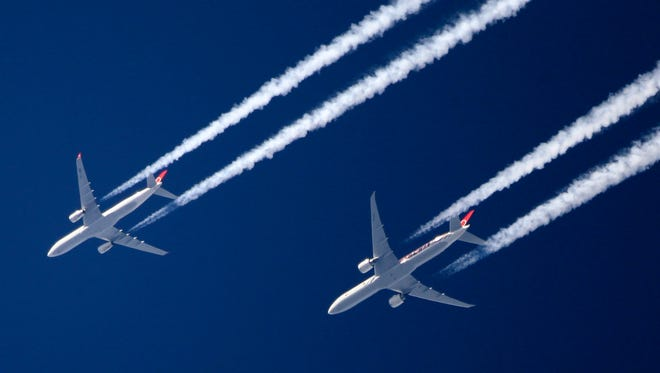 Two commercial airliners fly close together over London on March 12, 2012.