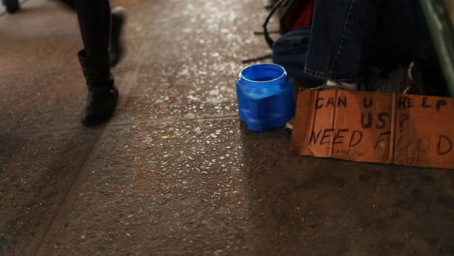 A sign of a man panhandling for money.