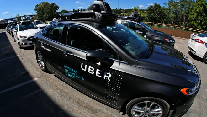 A group of self-driving Uber cars position themselves to take journalists on rides at Uber's Advanced Technologies Center in Pittsburgh on Monday.