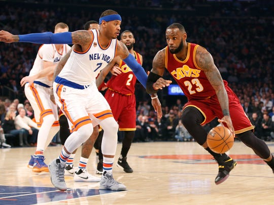 """Cleveland Cavaliers forward LeBron James driving to the basket with Carmelo Anthony defending, following Phil Jackson's comments about James and his """"posse""""."""