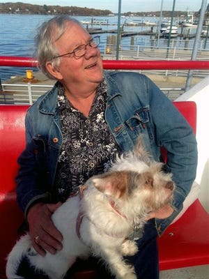 """In this undated photo provided by Caren Ferris, John Ferris rides with his adopted dog Ginger on a ferry to Peaks Island, Maine. Ferris, from Amherst, Mass., with his wife, adopted Ginger from the Aloft Hotel in downtown Asheville, N.C., where the couple were staying nearby when they met the 4-year-old terrier mix in the hotel bar sporting an """"Adopt Me"""" vest. The Aloft is believed to be the only hotel in the U.S. where guests can adopt the front desk dog."""