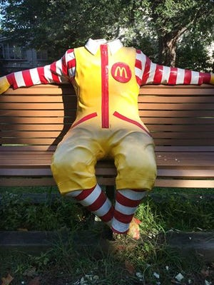 In this photo provided Thursday, Oct. 22, 2015, by Ronald McDonald House Charities, shows a decapitated Ronald McDonald statue sitting on a bench outside the Ronald McDonald House in Burlington, Vt., earlier in the month. The feet were also cut off the statue. Executive Director Kristine Bickford said that on three occasions vandals burned the statue's face, took off its head and sawed off its feet. The head was discovered dumped near the city's waterfront.