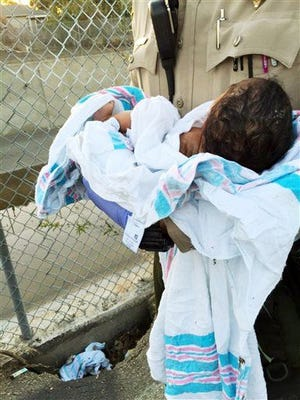 This Friday, Nov. 27, 2015 photo provided by the Los Angeles County Sheriff's Department shows an unidentified deputy holding an infant girl where she was found abandoned under asphalt and rubble, lower left, near a bike path in Compton, Calif., as they seek the public's help in identifying her. The baby girl, who was wrapped in a blanket, was believed to be only 36 to 48 hours old when two deputies found her Friday afternoon. She was taken to a hospital, where she is listed in stable condition.