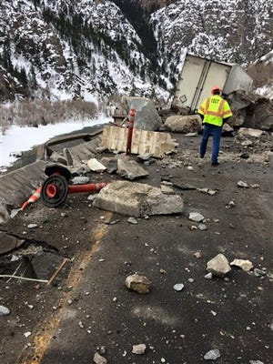 In this photo provided by the Colorado Department of Transportation a highway worker examines debris from a rock slide on Interstate 70 in Glenwood Canyon in western Colorado on Tuesday, Feb. 16, 2016. The rocks damaged the tractor-trailer rig visible in the background, but state officials said no one was injured. The interstate was closed in both directions while the canyon walls were inspected and the damage was repaired. (Colorado Department of Transportation via AP) MANDATORY CREDIT