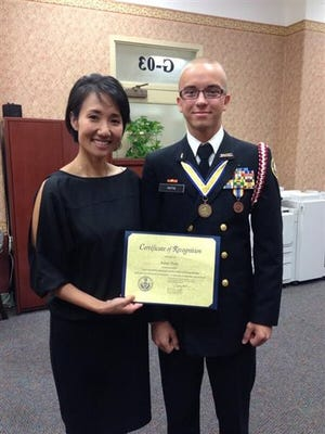 This May 2014 photo provided by Pennsylvania State Rep. Patty Kim shows Kim presenting a certificate to a man who identified as Harrisburg High School student Asher Potts. The school honors student just months from graduation was actually a 23-year-old Ukrainian national using a false identity after his visa expired, police said Thursday, Feb. 25, 2016. Artur Samarin, who used the alias Asher Potts, was arrested and charged Tuesday in Harrisburg, Pa., police said.