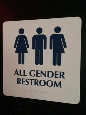 "An ""All Gender Restroom"" sign marks a bathroom in a bar."