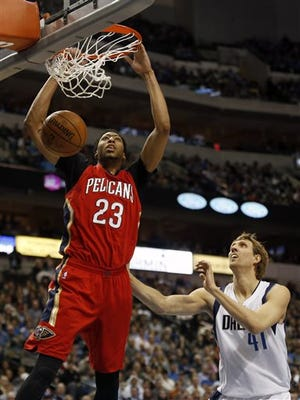 New Orleans Pelicans forward Anthony Davis (23) dunks in front of Dallas Mavericks forward Dirk Nowitzki (41) during the first half of an NBA basketball game, Saturday, Jan. 2, 2016, in Dallas.