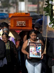 A woman walks with a photo of Martina Almazan in front of the coffin that contain Almazan's remains, in Tultepec, Mexico, Thursday, Dec. 22, 2016. A downtown Tultepec Catholic church hosted funeral Masses throughout the day Thursday for victims of the massive fireworks explosion at the San Pablito Market on Tuesday, that killed more than 30 people.