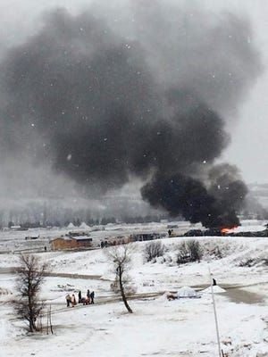 Dakota Access pipeline opponents burn structures in their main protest camp in southern North Dakota near Cannon Ball on Wednesday, Feb. 22, 2017, as authorities prepare to shut down the camp in advance of spring flooding season.