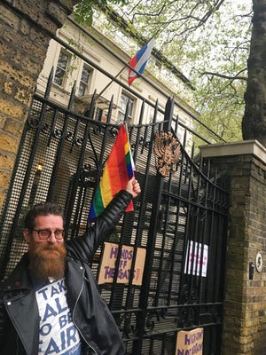 """A man poses outside the Russian Embassy in London, following reports of alleged torture and murder of gay men in Chechnya, Wednesday April 12, 2017.  In a statement the United Nations' High Commissioner for Human Rights called on the Russian government """"to put an end to the persecution of people perceived to be gay or bisexual"""", while Chechen authorities denied the reports, and spokesman for leader Ramzan Kadyrov insisted there were no gay people in Chechnya."""