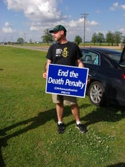 Scott Langley of Ghent, New York, holds a sign near the Cummins Unit prison near Varner, Arkansas, to protest executions set for Thursday, April 20, 2017. Arkansas adopted an aggressive schedule of eight executions in an 11-day period, but stays have been issued for four of the men initially set to die.