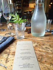 "This Aug. 24, 2016 photo shows a menu on a rustic wooden table at The Lost Kitchen in Freedom, Maine. The chef and owner Erin French got thousands of phone calls this year on April 1 when she opened reservations for the season for her 40-seat restaurant in an old mill in a tiny Maine town. French has just come out with a cookbook called ""The Lost Kitchen: Recipes and A Good Life Found in Freedom, Maine,"" telling the remarkable story of her career from a teenager working in her dad's diner to giving dinner parties in her apartment to running a successful restaurant."